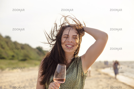 Happy adult woman with wine resting on beach