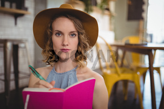 Portrait of confident young woman holding pink dairy