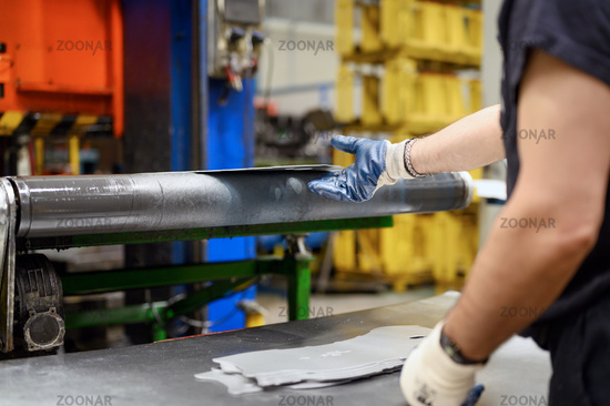 Close-up of male hands in working gloves working in metal processing factory. Worker using machinery in Steel industry, manufacturing, production.