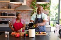 Serious african american senior couple cooking together in kitchen using compost bin