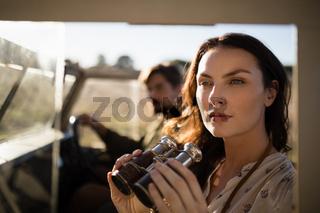 Thoughtful woman sitting with binoculars in vehicle