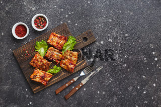 Grilled baked pork ribs with spices and vegetables on wooden cutting board on dark background. American food concept. Top view, copy space.