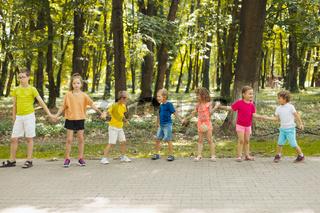 Summer camp kids making wave, holding hands together