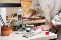 Creative female painter mixes palette of oil paints in palette. Close-up view