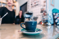 Cup of black coffee, spoon, wooden table, at a cafe