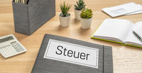 A folder on a desk with the label Taxes in german - Steuer