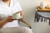 Happy lovely young female health worker laughing sincerely while holding cup of hot tea
