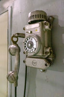 Old vintage wired telephone for communication hangs on textured gray wall. Antique phone from past for background