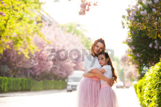 mom and daughter are standing next to a tender plant