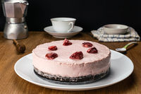 Side view of homemade delicious frozen strawberry cheesecake garnished with preserved dried strawberry in white ceramic dish.