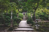 Path in park to small torii gate on Mount Misen in Miyajima, Hiroshima, Japan