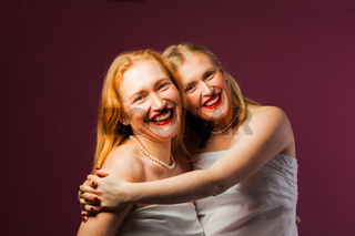Two pretty sisters hugging on purple background