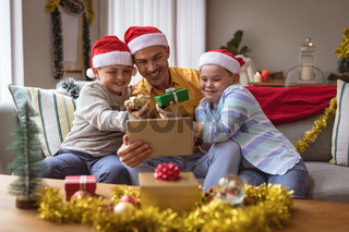 Caucasian father and two sons showing gifts during video call on digital tablet during christmas