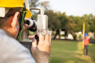 Surveyor engineer with partner making measure on the field