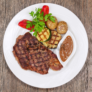 Grilled steaks, baked potatoes and vegetables on white plate on wooden background.