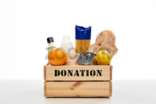 food donation in wooden box on table