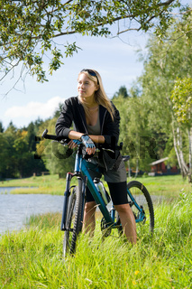 Mountain biking young woman relax by lake