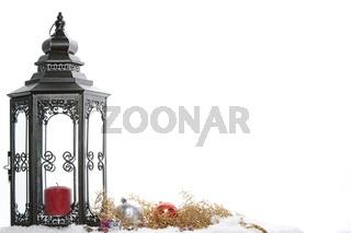 Goldene Weihnachtsdeko mit Laterne, Schnee, Geschenken und Kugeln