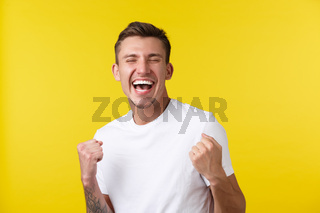 Lifestyle, summer and people emotions concept. Close-up portrait of rejoicing handsome happy guy feeling relieved over super good news, achieve goal or winning prize, yellow background