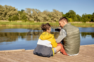 father and son taking selfie with phone on river