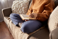 woman in warm sweater reading book at home