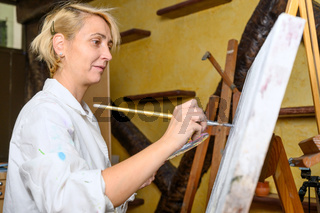 Happy woman paints on canvas using thin brush. Canvas stands on the easel. Artist draws at easel. Side view of female painting picture on canvas in art home studio