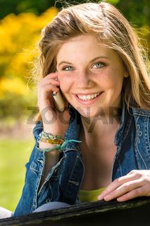Joyful adolescent girl using her mobile phone