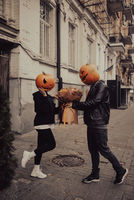 The guy gives his girlfriend a bouquet, both with a pumpkin head