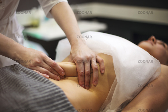 Young woman having stomach massage