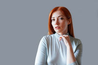 contemplative young woman with long red hair and light blue turtleneck