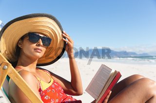Mixed race woman on beach holiday sitting in deckchair reading book