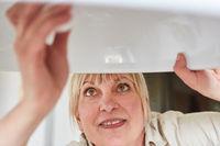 Frau als DIY Heimwerker wechselt eine Glühbirne