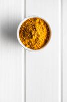 Indian turmeric powder. Turmeric spice. Ground turmeric in bowl.