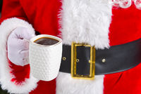 Santa claus holding white mug with coffee in his hand, close-up.