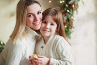 Joyful mother and lovely girl daughter in cozy knitted sweaters decorating Christmasmas fir tree with new year bauble