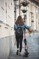 Electro-mobility. Rear view of female traveler exploring old town on environmentally friendly electric scooter.