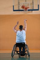 a war invalid in a wheelchair trains with a ball at a basketball club in training with professional sports equipment for the disabled. the concept of sport for people with disabilities