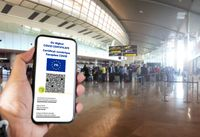 French EU Digital COVID Certificate with the QR code on the screen of a mobile held by a hand with blurred airport in the background