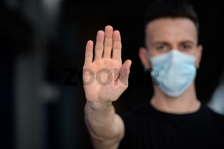 Hand of young handsome man showing STOP gesture while wearing face mask to protect from corona virus outdoors