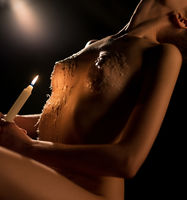 Naked woman with candle in the dark low angle shot
