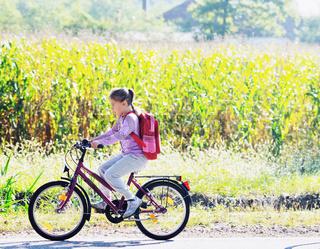 schoolgirl traveling to school on bicycle