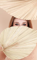 Young woman covering face with fan