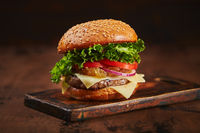 Homemade burger with beef, cheese and onion marmalade on a wooden board. Fast food concept, american food