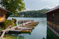Rental row boats on pier at mountain lake Walchensee in Bavaria, Germany on sunny day with boat house