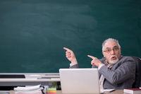 Old male teacher in front of blackboard