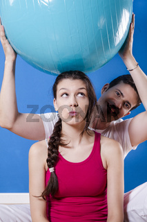 Happy athletic couple with fitness ball.
