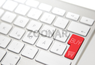 White computer keyboard with red 'buy' button