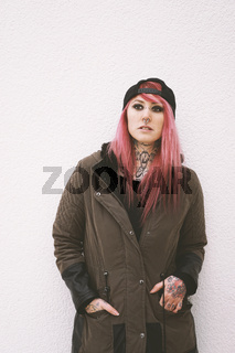 young woman with pink hair piercings and tattoos leaning against wall