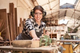 Frau als Schreiner Lehrling beim Holz hobeln