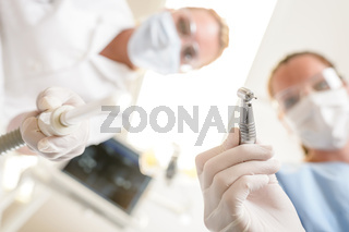 Female dentist and assistant focus on drill